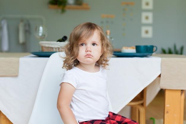 Uma menina sentada e triste, retrato emocional. Foto Premium
