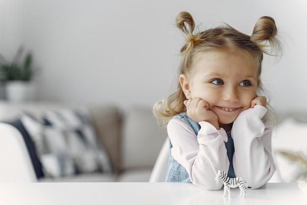 Uma menina sentada em uma mesa com brinquedo Foto gratuita