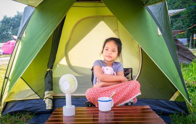 Uma menina sentada na barraca ao ir acampar. o conceito de atividades ao ar livre e aventuras na natureza. Foto Premium