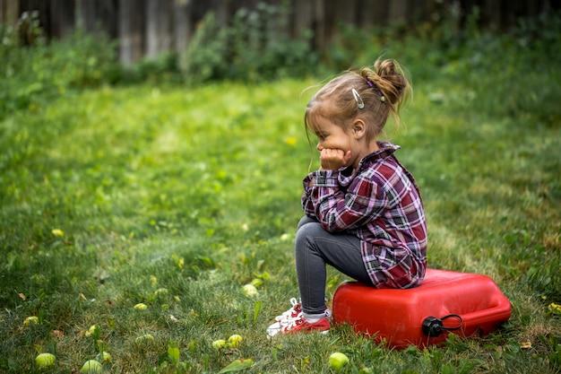 Uma menina sentada na vasilha vermelha, uma emoção triste Foto Premium
