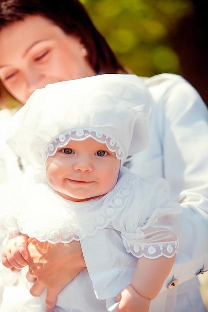 Uma menina sentada nas mãos da mãe Foto Premium