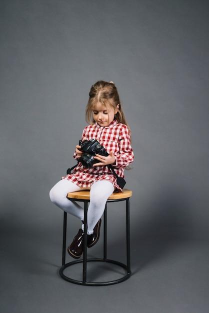Uma menina sentada no banquinho olhando para a câmera contra um fundo cinza Foto gratuita