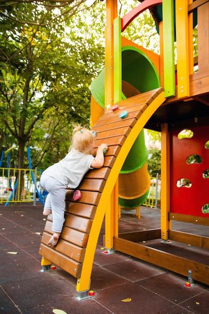 Uma menina sobe a parede de escalada na corrediça das crianças no campo de jogos. Foto Premium