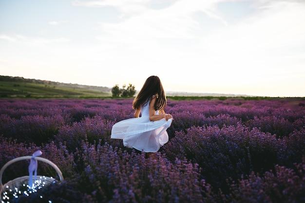 Uma menina vestida de vestido branco no campo de lavanda Foto Premium
