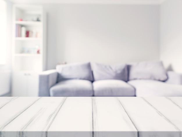 Uma mesa branca vazia na frente do sofá borrão na sala de estar Foto gratuita