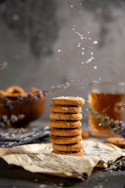 Uma mesa de frente com biscoitos e com chá na mesa cinza biscoito chá biscoito doce Foto gratuita