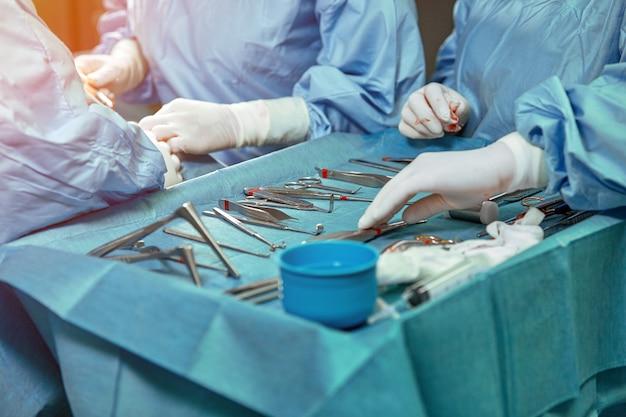 Uma mesa de sala de cirurgia estéril com instrumentos para cirurgia localizados nela. as mãos dos cirurgiões em luvas brancas mudam de ferramenta. Foto Premium