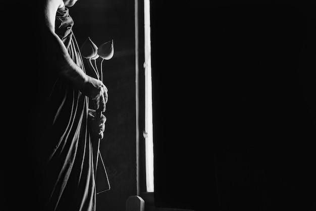 Uma monge budista que prende uma flor de lótus usada para rituais do budismo. Foto Premium