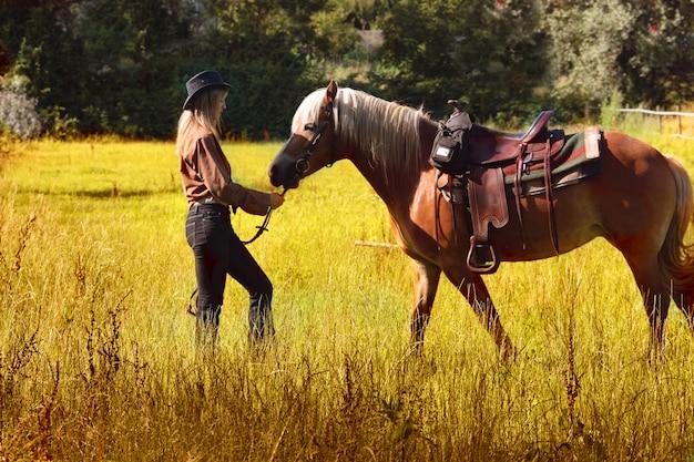 Uma mulher a cavalo na zona rural Foto Premium