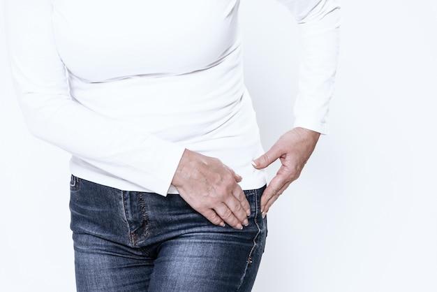 Uma mulher adulta tem um quadril dolorido no quarto branco. Foto Premium
