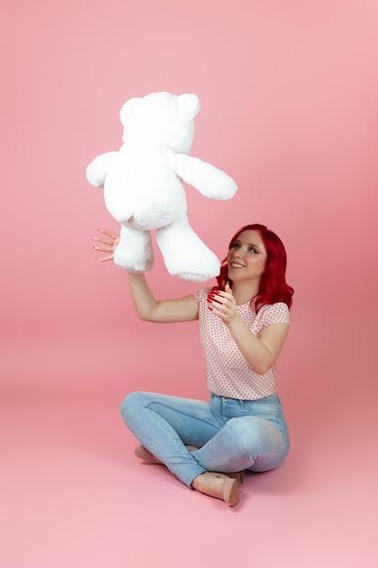 Uma mulher alegre e brincalhona, de cabelo vermelho e vestindo jeans joga um grande ursinho de pelúcia branco Foto Premium