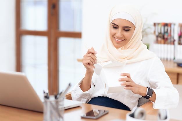 Uma mulher árabe em um hijab está almoçando. Foto Premium