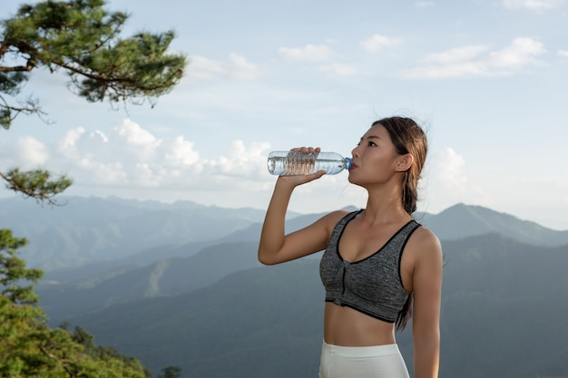 Uma mulher asiática bonita que meditating e que exercita na parte superior da montanha. Foto gratuita