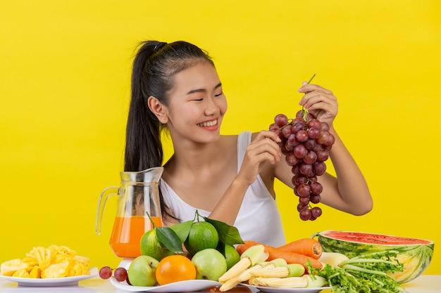 Uma mulher asiática vestindo uma camiseta branca. a mão esquerda segura um cacho de uvas. a mão direita pega as uvas para comer e a mesa está cheia de várias frutas. Foto gratuita