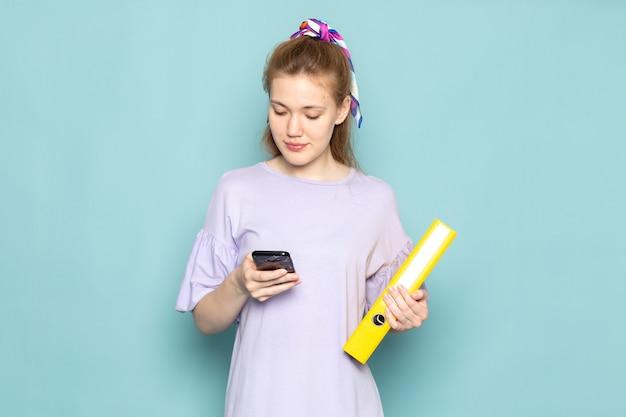 Uma mulher atraente, de frente, em vestido de camisa azul, segurando arquivos amarelos e usando um telefone em azul Foto gratuita