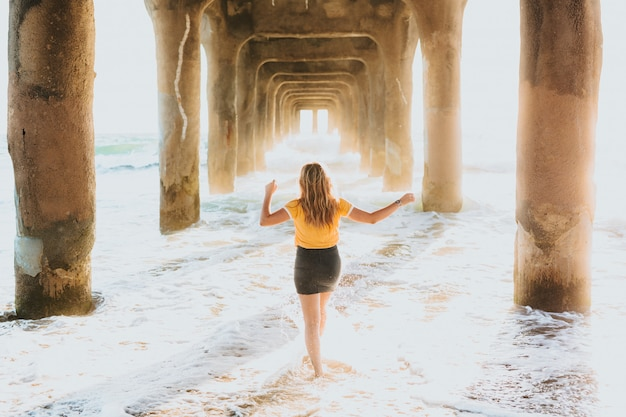 Uma mulher atraente em uma camiseta amarela e shorts curtos em pé sob um grande cais de pedra Foto gratuita