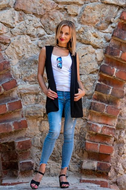 Uma mulher bonita, com longos cabelos loiros, blusa branca e calça azul na parede de pedra da cidade velha Foto Premium