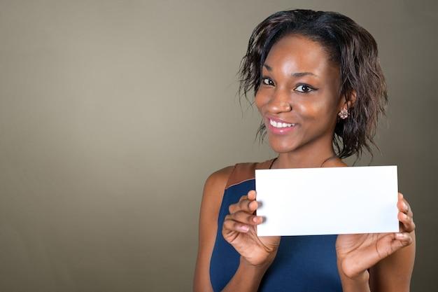 Uma mulher bonita com um sorriso perfeito detém um cartão Foto Premium