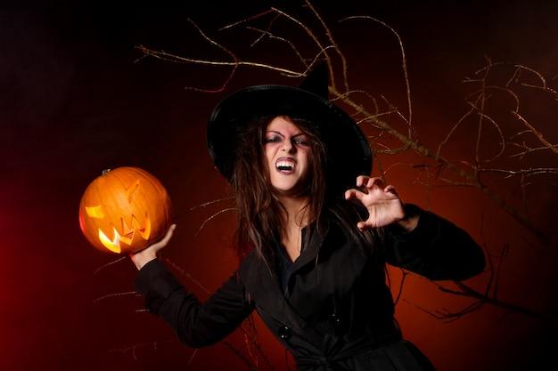 Uma mulher bonita com uma abóbora na mão Foto gratuita