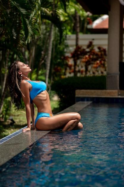 Uma mulher bonita com uma figura esbelta senta-se perto da piscina com os olhos fechados e as pernas na água Foto Premium