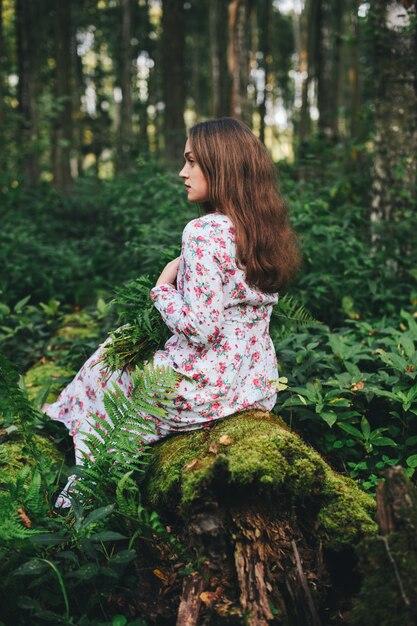 Uma mulher bonita em um vestido floral está sentada com um buquê de samambaia na floresta. Foto Premium