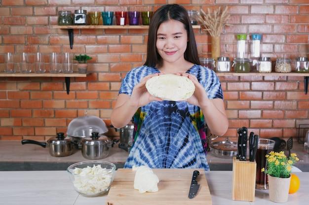 Uma mulher bonita está cortando vegetais na cozinha em casa. Foto gratuita