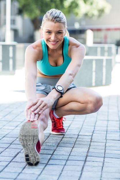 Uma mulher bonita esticando sua perna Foto Premium