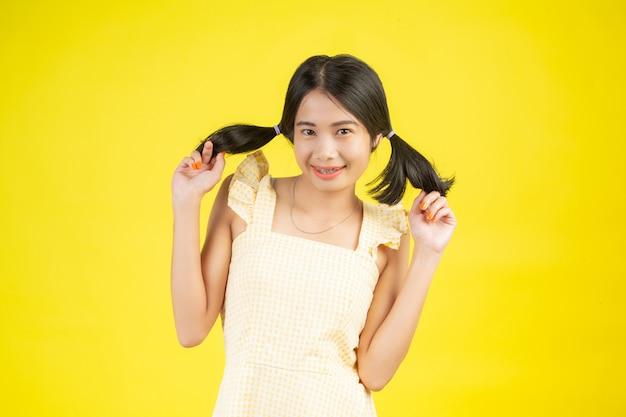 Uma mulher bonita que está feliz mostrando vários gestos em um amarelo. Foto gratuita