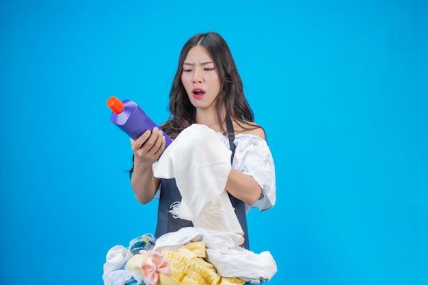 Uma mulher bonita, segurando um pano e detergente líquido preparado para lavar no azul Foto gratuita