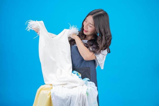Uma mulher bonita, segurando um pano preparado para lavar em azul Foto gratuita