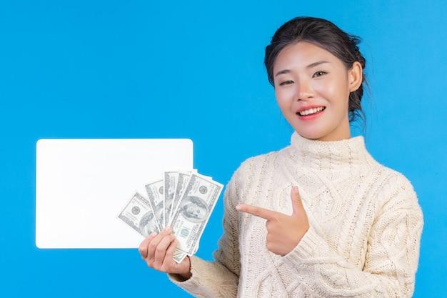 Uma mulher bonita vestindo um novo tapete branco de mangas compridas, segurando uma placa branca e uma nota de dólar em um azul. negociação. Foto gratuita