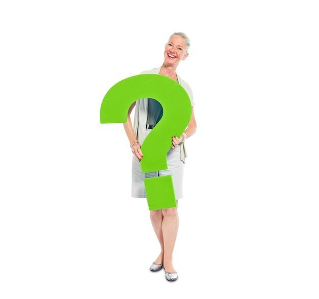 Uma mulher casual, segurando um ponto de interrogação verde Foto gratuita