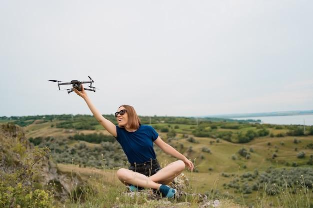 Uma mulher caucasiana com um drone na mão, sentado em uma colina rochosa verde com céu no fundo Foto gratuita