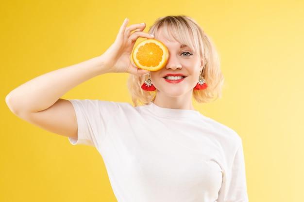 Uma mulher com laranjas nos olhos. lábios de batom vermelho. menina alegre e alegre exala laranjas positivas e mimadas. isolado em fundo amarelo Foto Premium