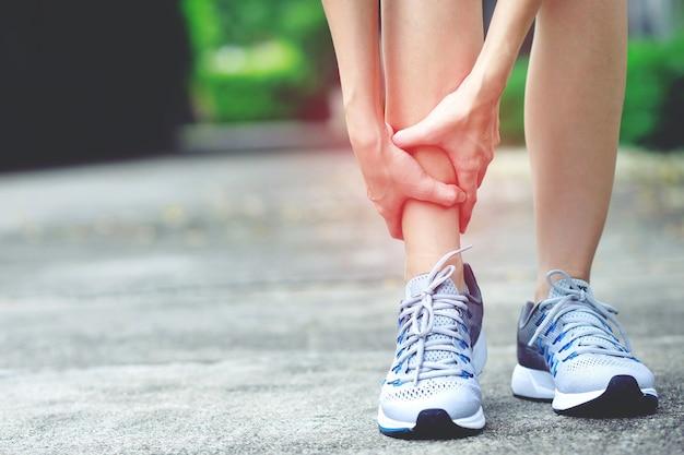 Uma mulher com muita dor na perna no parque Foto Premium