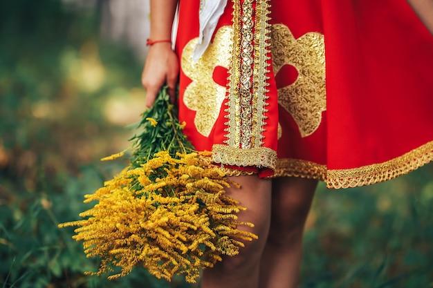 Uma mulher com roupas nacionais russas segurando um lindo buquê de flores amarelas Foto Premium