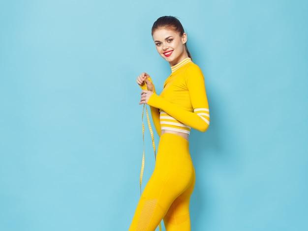Uma mulher com um agasalho elegante pratica esportes e faz exercícios, um agasalho amarelo Foto Premium