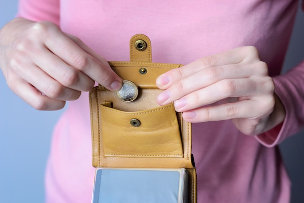 Uma mulher com um suéter rosa coloca uma moeda em uma bolsa aberta. Foto Premium