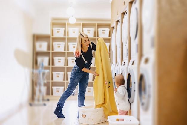 Uma mulher com uma criança coloca os lençóis na lavanderia Foto Premium
