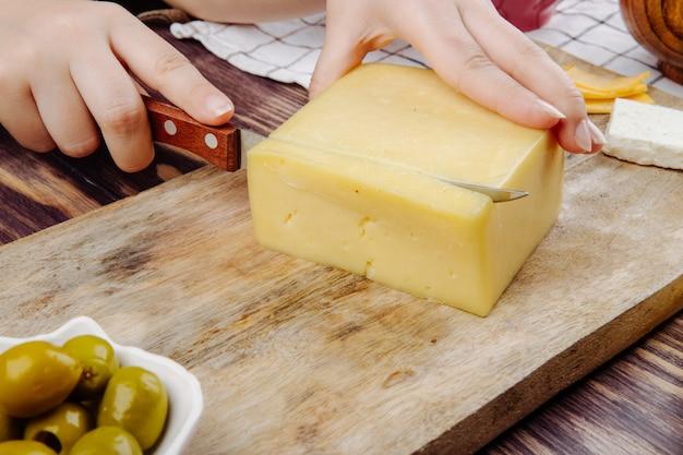 Uma mulher corta queijo holandês em uma placa de madeira vista lateral Foto gratuita