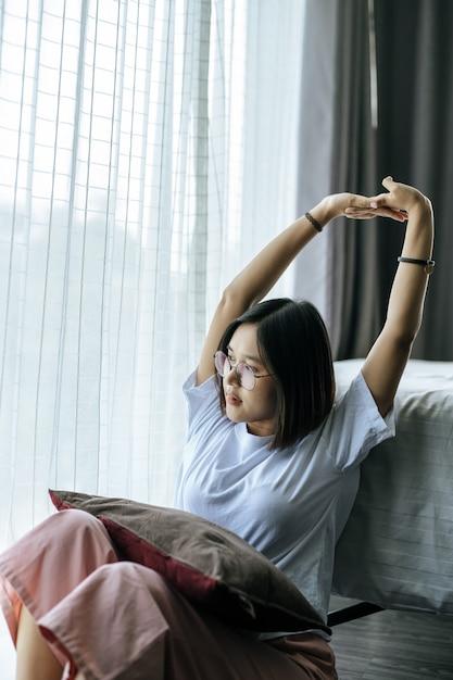 Uma mulher de camisa branca, sentada na cama e levantando os dois braços. Foto gratuita