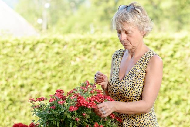 Uma mulher de meia idade com uma planta no jardim Foto Premium
