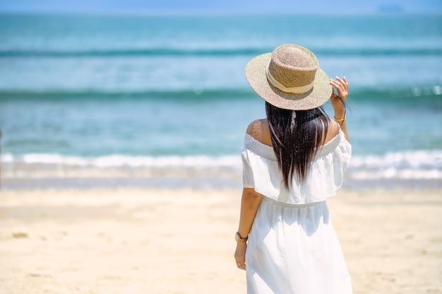 Uma mulher de pé na praia de costas Foto Premium