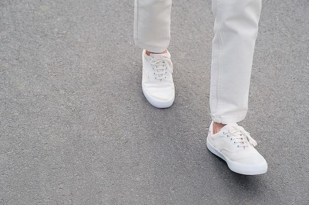 Uma mulher de tênis está na calçada. pernas de uma garota com jeans e tênis brancos novos. estilo de vida moderno e elegante. Foto Premium