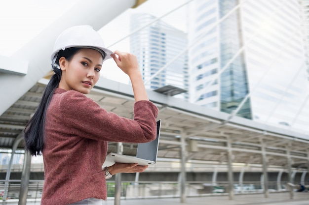 Uma mulher de trabalho asiática confiante está usando um capacete e está trabalhando em um laptop em pé ao ar livre. Foto Premium