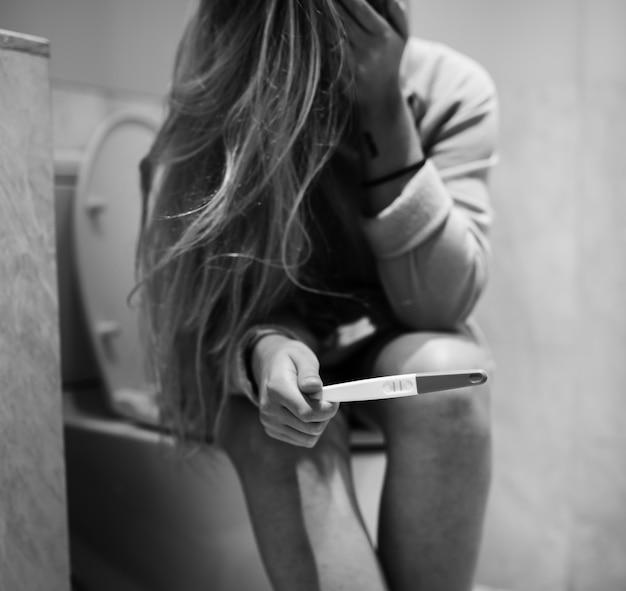 Uma mulher deprimida com um teste grávido positivo Foto gratuita