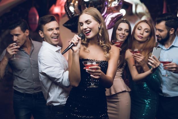 Uma mulher em um vestido preto está cantando músicas com seus amigos. Foto Premium