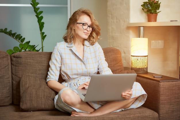 Uma mulher em um vestido sentado no sofá com as pernas cruzadas funciona remotamente em um laptop. uma garota feliz assistindo a um webinar em seu apartamento. Foto Premium