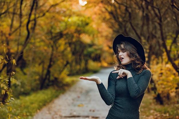 Uma mulher engraçada em um chapéu preto e um vestido verde fica no parque no outono no caminho Foto Premium