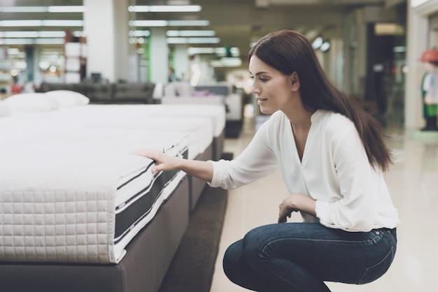 Uma mulher escolhe um colchão em uma loja. Foto Premium